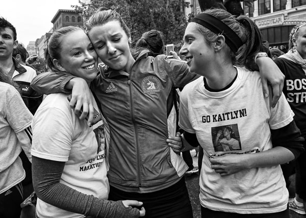 (05/25/13-Boston,MA)  Kaitlyn Brant, who ran the April 15th marathon with her dad, pauses as she crosses the Boston Marathon finish line today, May 25, 2013, flanked on each side by from left Jessica Campbell and Courtney Haskell during the Boston Strong OneRun in remembrance of those who didn't finish the race April 15.
