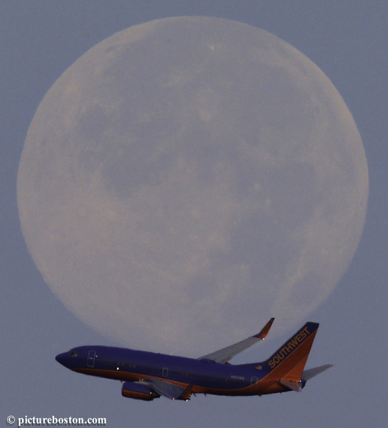 The Supermoon fades into a Boston morning sky shortly before moonset on August 11, as a Southwest Airliners jet departs Logan airport.