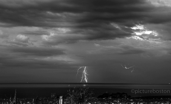 Lightning exits the Massachusetts east coast between Winthrop and Quincy, during the last of the thunderstorms, Tuesday evening.