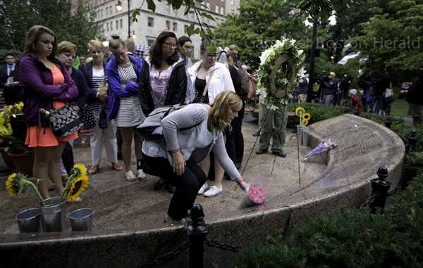 09/11/2015-Boston,MA. Relatives and friends of the Massachusetts' victims of the September 11 terror attacks, place flowers at the Friday morning's ceremony at the Massachusetts 911 memorial. Staff Photo by Mark Garfinkel