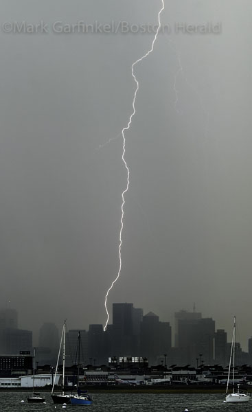 August 18, 2015. Lightning strikes over and to the rear of 1 International Place in Boston Tuesday afternoon as a line of thunderstorms pushed through.