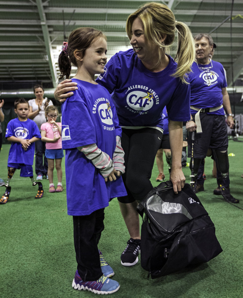 11/14/2015-Boston,MA. Heather Abbott, who lost her leg in the Boston Marathon bombing of 2013, hugs Kori Tickel, an 8 year old amputee from Somerset, at the 3rd Ossur Boston Running and Mobility Clinic, Saturday morning. The Heather Abbott Foundation delivered a grant to Kori so she could get the prosthetic. Staff photo by Mark Garfinkel