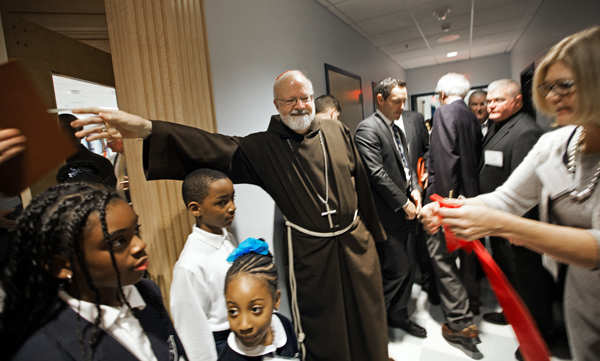 12/02/2015-Boston,MA. Cardinal Sean O'Malley reaches for the Book of Prayers prior to blessing the newly re-dedicated Saint John Paul 11 Catholic Academy Lower Mills Campus, on Dorchester Ave. Staff photo by Mark Garfinkel