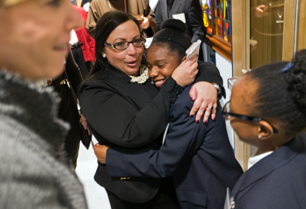 12/02/2015-Boston,MA. Lisa Warshafsky, Principal of Saint John Paul 11 Catholic Academy Lower Mills Campus, hugs student Orianeh Byron Gabelus at the re-dedication of the school on Dorchester Ave. Staff photo by Mark Garfinkel